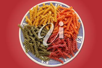 Plate with four flavors of italian fusilli pasta. Food background.