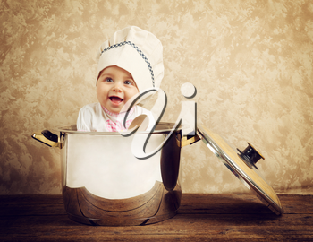 Cute baby chef in a huge cauldron on wooden table