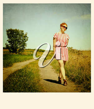 Red hair woman standing in a path.  Cross processed to look like and aged instant picture